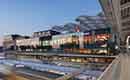 Transparant Retailpaviljoen bovenop treinsporen naast Utrecht CS